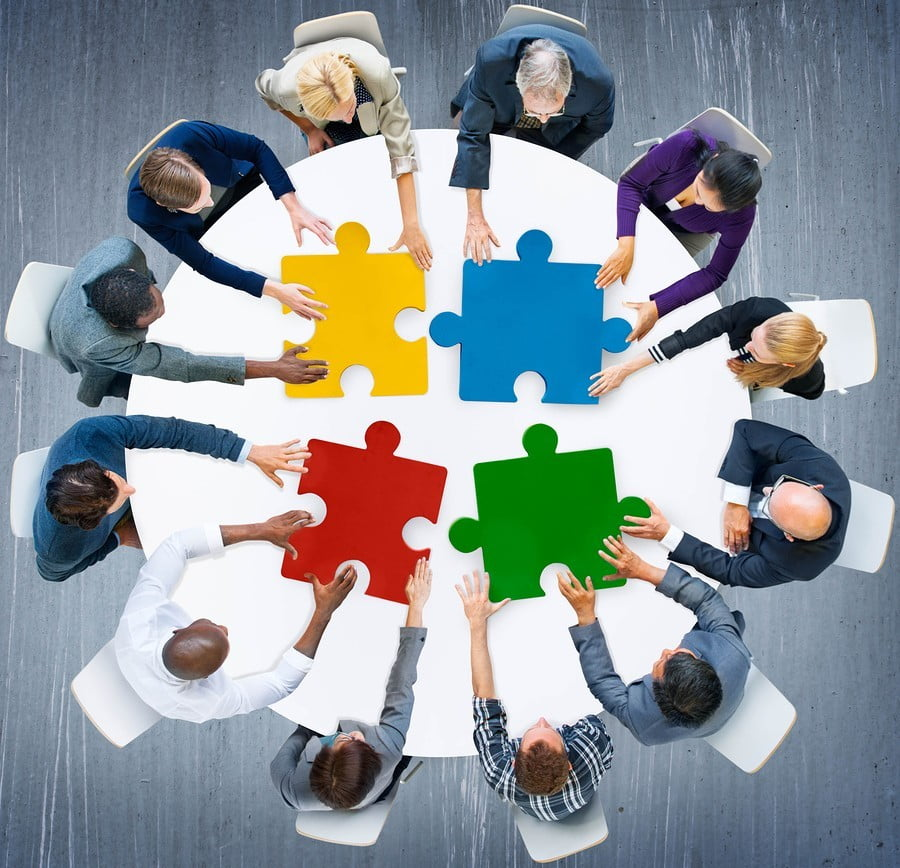 a team sitting around a round table building a giant colourful puzzle